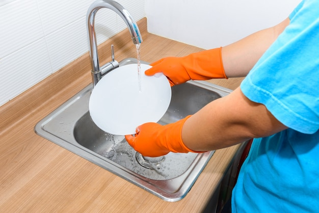 Close up hands of man washing dishes