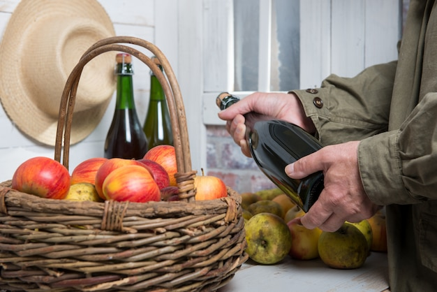 Close up of hands man with a bottle of cider and apples