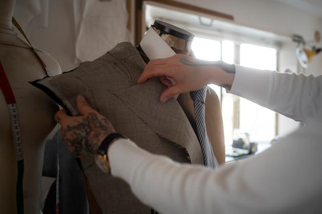Закройте руки, производящие одежду