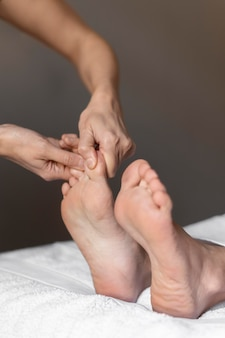 Mani del primo piano che massaggiano i piedi