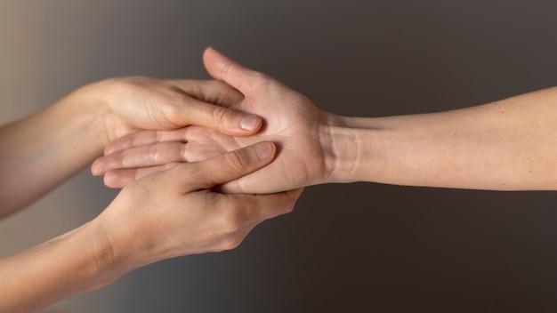 Close-up hands massaging palm