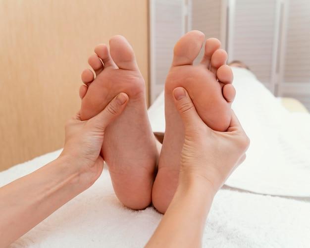 환자의 발을 마사지하는 손을 닫습니다