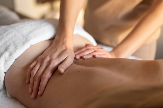 Close-up hands massaging person's back