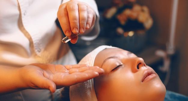 ウェルネススパセンターで女性の顔にスキンケア手順用のアンプル製品を使用して、女性の美容師の手をクローズアップします。