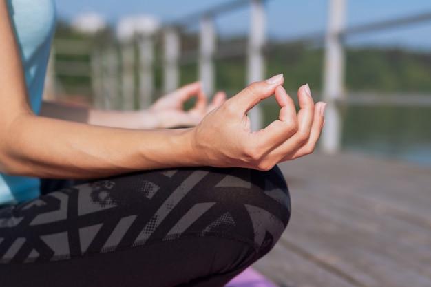 Крупным планом руки молодой женщины, которая медитирует, сидя в позе лотоса на пирсе