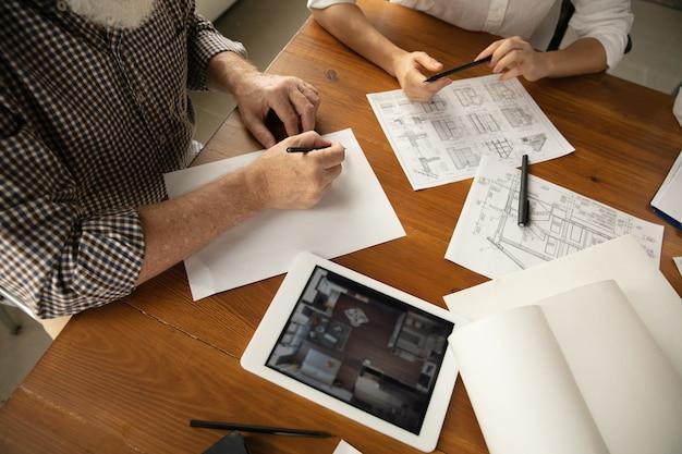 Закройте руки инженера-архитектора и молодой пары во время презентации будущего дома. стол вид сверху с документами, план. первый дом, промышленное здание, концепция. переезд на новое место жительства.