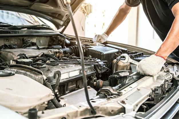 自動車整備士の手をクローズアップは、車のエンジンの修理とメンテナンスにレンチを使用しています