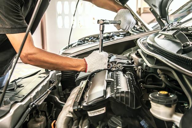 Крупным планом руки автомеханика, использующего гаечный ключ для обслуживания двигателя автомобиля.