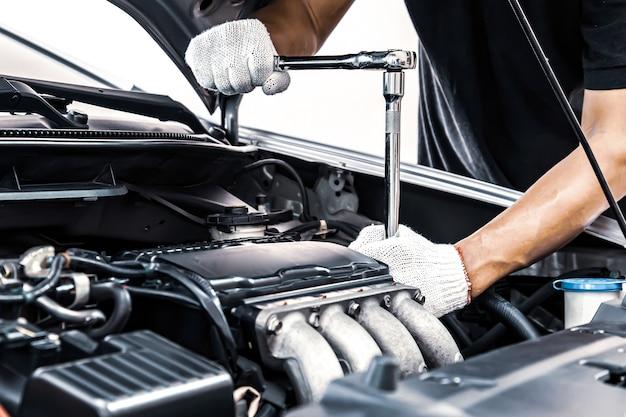 車のエンジンをメンテナンスするためにレンチを使用して自動車整備士のクローズアップの手。