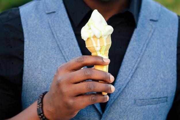 スタイリッシュな黒人男性のクローズアップの手は、夏の公園での会議に適しています。アフリカ系アメリカ人の友人のヒスパニック系ビジネスマンは、屋外のワッフルホーンピクニックでバニラホワイトの甘いアイスクリームを持っています。