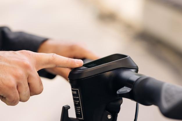 Крупным планом руки бизнесмена включает электрический самокат мужчина нажимает кнопку пуска