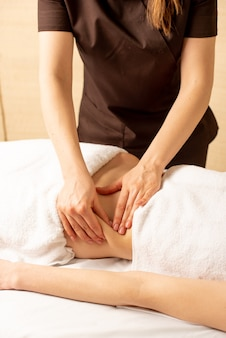 カイロプラクターやマッサージ師の手をクローズアップして、クリニックのインテリアで横になっている女性のために胃のリラックスマッサージを行います。