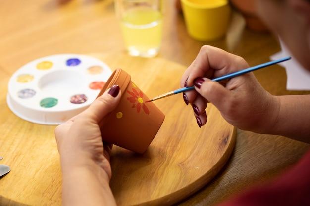 アートホームスタジオの粘土セラミックポットに女性アーティストの絵の具の手をクローズアップ