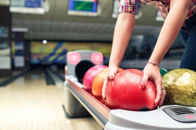 女の子のクローズアップの手はボウリング球を取ります。