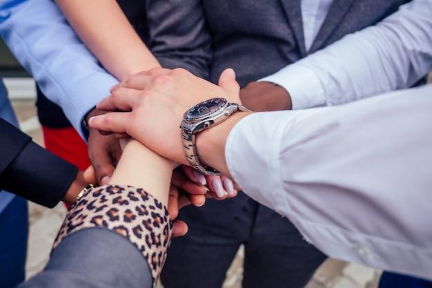 ビジネス会議の握手で多国籍企業の実業家とビジネスマンのグループの手を閉じます。チームワークの概念