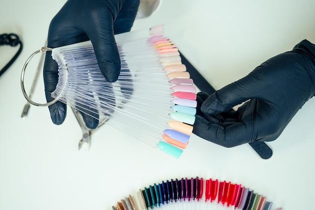 Крупным планом руки мастера маникюра профессионального мастера маникюра женщина в белом пиджаке и черных резиновых перчатках выбирает палитру цветов лака для ногтей в салоне красоты спа.