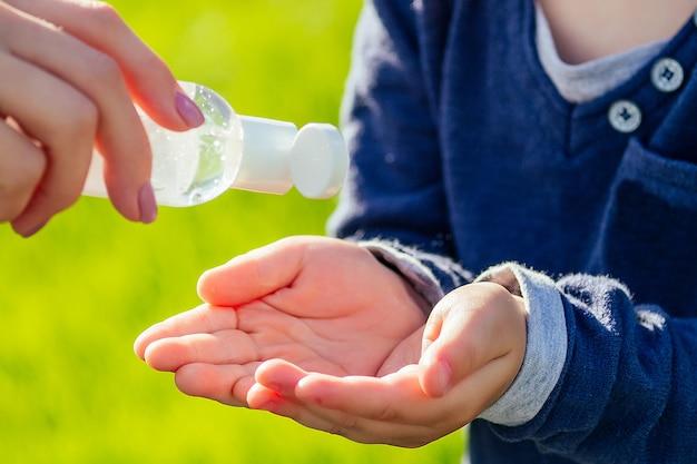 母親のクローズアップの手は、緑の草を背景に公園で息子の手に消毒ジェル(抗菌ジェル)を適用します