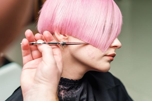 Крупным планом руки профессионального парикмахера стрижут розовые волосы ножницами