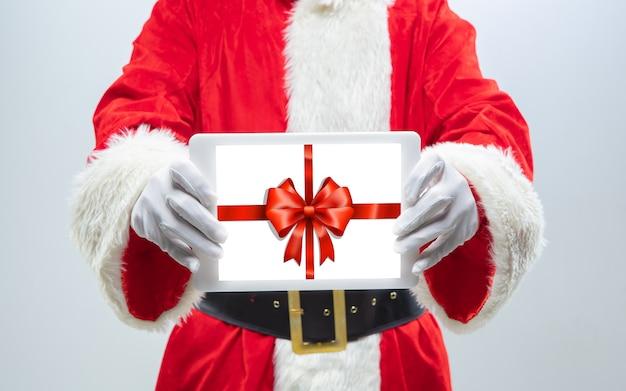 画面上のギフトの装飾とデバイスを保持しているサンタクロースの手を閉じます。冬のセール、2021年の新年とクリスマスのお祝い、最新のデバイスとガジェット、オンラインショッピングのコンセプト。