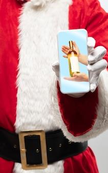 画面上でワインを与える手でサンタクロース保持装置の手を閉じます。冬のセール、2021年の新年とクリスマスのお祝い、最新のデバイスとガジェット、オンラインショッピングのコンセプト。