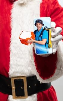 画面上の幸せな配達員と一緒にデバイスを保持しているサンタクロースの手を閉じます。冬のセール、2021年の新年とクリスマスのお祝い、最新のデバイスとガジェット、オンラインショッピングのコンセプト。