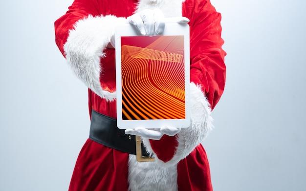 画面に新しい装飾が施されたサンタクロースの保持装置の手を閉じます。冬のセール、2021年の新年とクリスマスのお祝い、最新のデバイスとガジェット、オンラインショッピングのコンセプト。