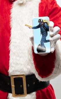 画面に乗っている配達員と一緒にサンタクロースの保持装置の手を閉じます。冬のセール、2021年の新年とクリスマスのお祝い、最新のデバイスとガジェット、オンラインショッピングのコンセプト。