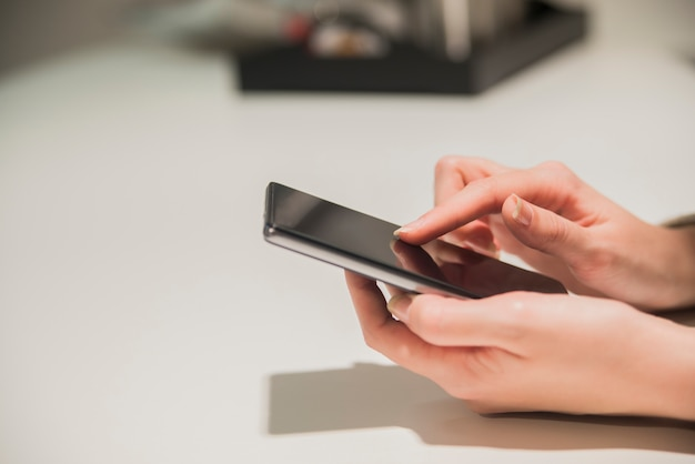 Крупным планом руки девушки, сидя за деревянным столом, в одной руке - смартфон. предприниматель, занимающийся серфингом в интернете на смартфоне.