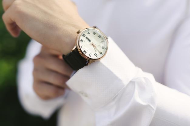 時計と新郎のクローズアップ手