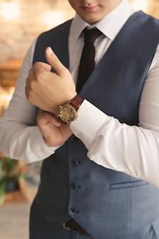 時計と新郎のクローズアップの手