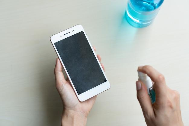 Закройте руки женщины, дезинфицирующей смартфон путем распыления алкоголя из бутылки, защиты от инфекционных вирусов, бактерий и микробов. концепция здравоохранения.