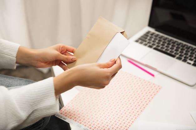 Закройте руки женщины, открывающей, получая поздравительную открытку на новый год и рождество 2021 года от друзей или семьи. читаем письмо с наилучшими пожеланиями, открываем конверт. праздники, торжество.