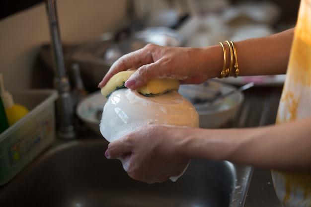 일에서 흐르는 물에서 설거지하는 여자의 손을 클로즈업합니다