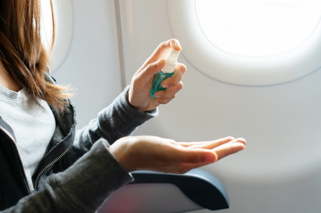 Закройте вверх руки женщины, распыления алкоголя из бутылки на ее руку на плоскости, защита от инфекционных вирусов, бактерий и микробов. концепция здравоохранения.