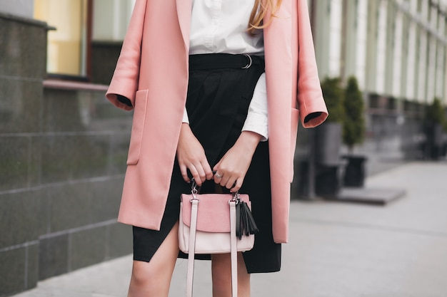 Крупным планом руки женщины, идущей по городской улице в розовом пальто