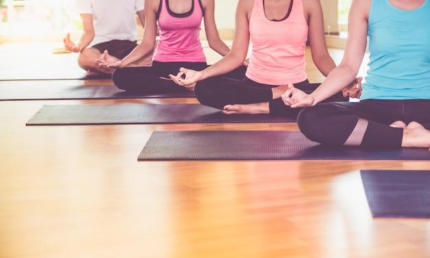 手のマドラをして座っているヨガグループの手を閉じて、トレーニングスタジオのフィットネスルームで瞑想する