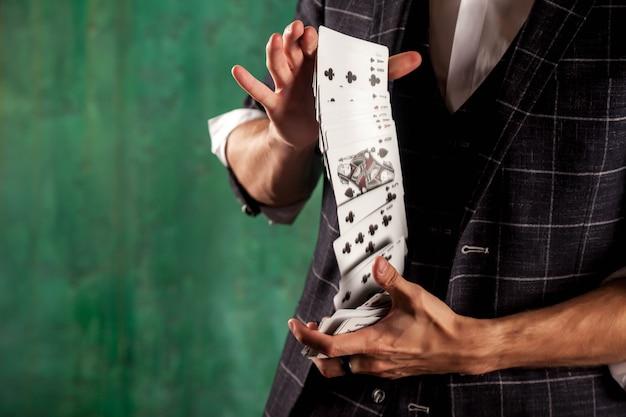 Крупным планом руки молодого человека с азартными играми. красивый парень показывает фокусы с картой. умные руки фокусника на зеленой предпосылке текстуры. понятие о развлечениях и увлечениях. копировать пространство