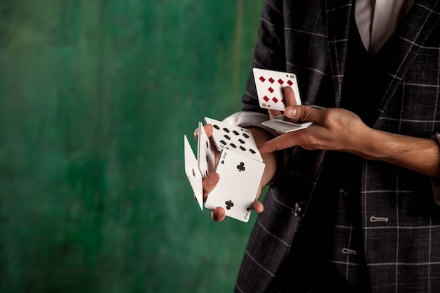Крупным планом руки молодого человека с азартными играми. красивый парень показывает фокусы с картой. умные руки фокусника