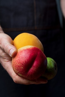 Close-up of hands offering fresh and raw fruits.