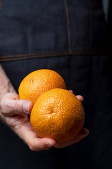 Close-up of hands offering fresh and raw oranges.