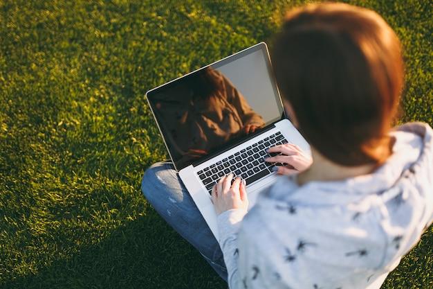 키보드에 손을 닫습니다. 야외에서 푸른 잔디 햇살이 비치는 잔디밭에 있는 공원의 공간을 복사하기 위해 빈 검은색 빈 화면이 있는 노트북 컴퓨터에서 일하는 여성. 모바일 오피스. 프리랜서 비즈니스 개념입니다.
