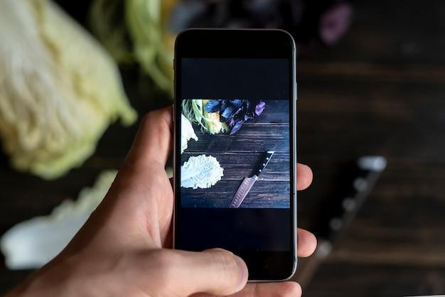 전화로 음식 제품 사진을 만드는 어두운 테이블 위에 손을 닫습니다