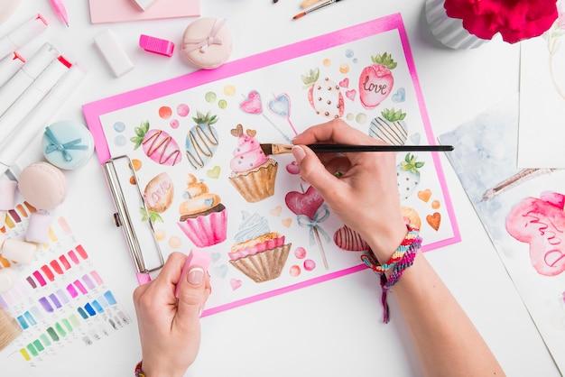 Макро руки, рисующие кекс