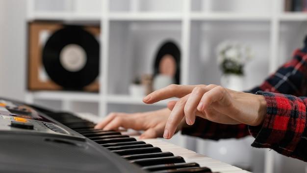 Close-up hands playing at digital piano