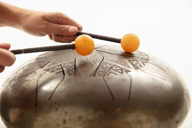 A close up of hands playing the hank drum on white studio background