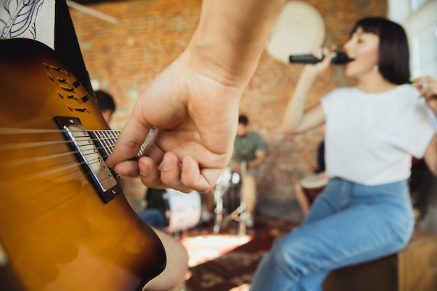 Close up hands playing musician band jamming together in art workplace with instruments