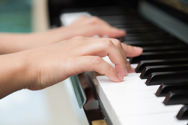 Primo piano delle mani che giocano pianoforte