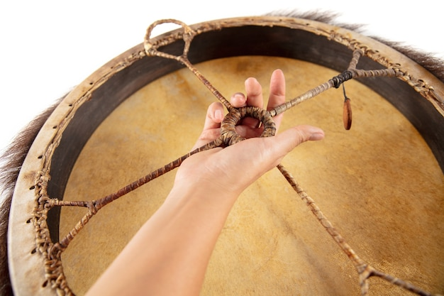 A close up of hands playing the tambourine percussion on white studio background