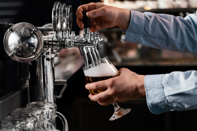 Mani del primo piano che versano birra in vetro