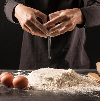 小麦粉に卵を注ぐクローズアップ手